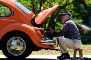 Howard Boykin replaces an air hose on his 1971 Volkswagen Beetle in front of his home in Anderson, S.C.