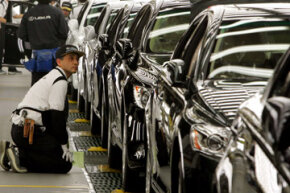 A Toyota Motor Corp. worker kneels down to check a Lexus at the Japanese automaker's flagship production line for luxury Lexus models in Tahara, central Japan.