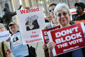 Demonstrators hold signs during a rally against voter ID laws, Sept. 13, 2012 in Philadelphia.