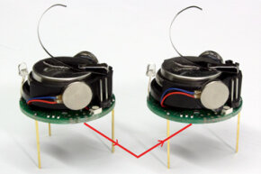 The Kilobot on the left is transmitting a signal by bouncing it off the table to the Kilobot on the right, which receives it.