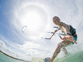 A young woman kiteboards under the sun.