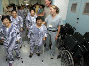 Patients suffering from bone diseases walk with the help of nurses and U.S. volunteers after undergoing joint replacement surgeries at the West China Hospital of Sichuan University.
