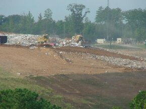 Trash is being loaded and compacted in a landfill.