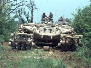 A remotely controlled Panther armored mine-clearing vehicle leads a column of armored vehicles down a road near McGovern Base, in Bosnia-Herzegovina on May 16, 1996.