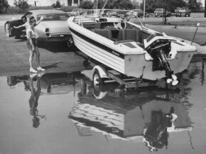 A couple works together to launch a boat from a trailer.