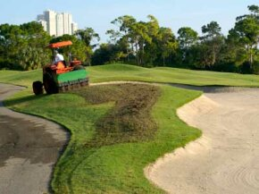 A tractor aerates a golf course, leaving behind plugs of soil in its path.