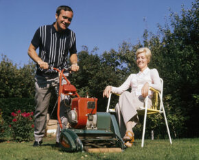 Chelsea Football Club player Ron Harris mows his lawn as his wife watches at their home in England in 1970. Mr. Harris appears to have a warm-season grass growing in his remarkable yard, possibly Bermuda.