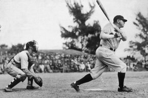 Babe Ruth swings at bat as a catcher crouches behind him during a game circa 1925.