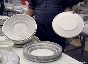 This metal mold is prepped and ready to be filled. Notice the finished production plate mold on the right.