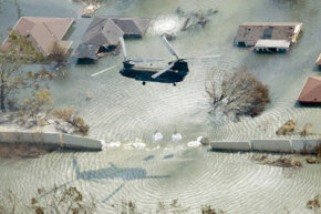 A helicopter drops sand bags to plug a levee break in New Orleans following the landfall of Hurricane Katrina in 2005.