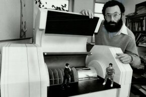 It detects quarks! The late theoretical physicist Nathan Isgur displays a model of part of a machine for observing the behavior of quarks. The price tag (back in 1981) was $83 million.