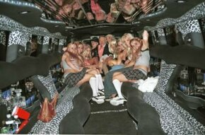 Hugh Heffner and friends pose in the highly stylized Playboy limousine. A swank limo interior with neon lighting