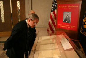 President George W. Bush looks over the Emancipation Proclamation on display at the National Archives Jan. 16, 2006, in Washington, DC. The document is rarely displayed due to its fragile condition.