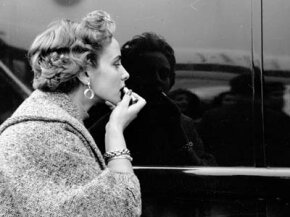 "A contestant in a ""Miss World"" beauty competition applies her lipstick using a shiny car as a mirror, November 1953."