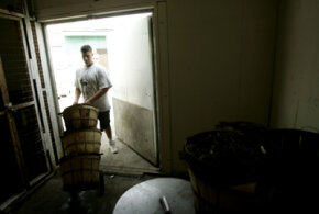 Kevin Doane rolls a cart of freshly caught Maryland Blue Crabs into a walk in freezer on August 3, 2005.