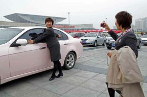 Salespeople from the Anhui province in China, pose for pictures in front of a pink sedan, an award for the best sales team, during the Mary Kay China Leadership Conference.