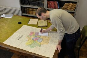 A man researches family history with a map in Bath Records Office, England.