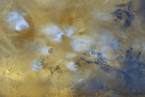 Mars Global Surveyor view of the Tharsis region showing the volcanoes (covered by blue-white clouds) and the Valles Marineris canyon (lower right)