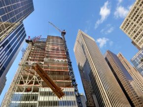 Skyscraper under construction with steel beam on crane, low angle view