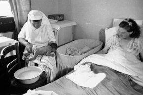 A midwife tends to the baby after a home birth in the 1940s.
