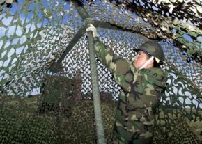 An airman in the U.S. Air Force covers military trucks with camouflage netting.