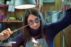 Glass artist Elena Rosso twists a zanfirico glass cane in Venice, Italy. Twisting different colors of molten glass together allows artists to create the patterns they desire.