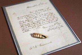A replica of one of George Washington's dentures is shown along with a copy of his letter written to his dentist Mr. Greenwood thanking him for his attentiveness. Greenwood made this denture from a gold plate with ivory teeth riveted to it.