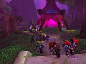 A large group of World of Warcraft characters in player-versus-player mode attacks the night elf capital city of Darnassus.