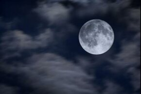 A full moon visible through clouds.
