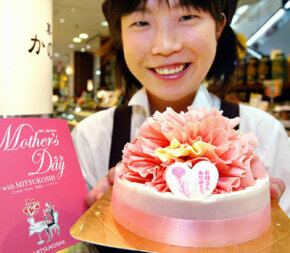 A confectionery shop employee displays a cake decorated with red carnation-shaped chocolate in Tokyo on May 7, 2004. For Mother's Day, white carnations represent a mother who has died, while red carnations represent a mother who is still living.