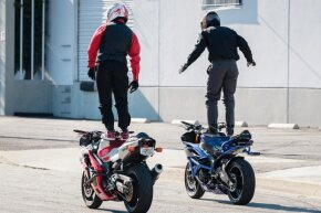 Two people stand on a motorcycle. It may seem like a dangerous feat, but in 2013, Captain Abhayjit Mehlawat did it on a moving motorcycle for 9 miles.