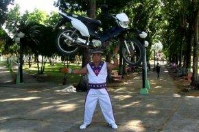 Gerard Jessie balances a motorcycle on his head.