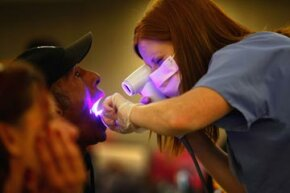 Dental hygiene student Audrey Rayniak gives an oral cancer screening to Kevin Smith at a free dental clinic in Brighton, Colo.