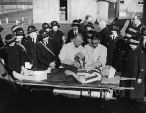 Old-school doctors demonstrating how patients contaminated by mustard gas are washed as soon as they reach the hospital.