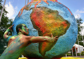 """The origins of """"America"""" are bit obscure. A dancer performs next to a globe during the UN Climate Change Conference in 2007."""