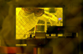An engineer prepares a silicon wafer in an early stage of microchip production.