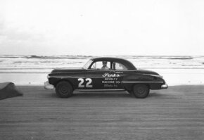 RacingOne/Getty Images Red Byron on Daytona Beach, Fla., in 1950. He won the first Strictly Stock race in 1949 in a similar Oldsmobile coupe. See more NASCAR images.