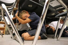 Third-grade students in San Francisco take cover under desks as they participate in the 'Great California ShakeOut' earthquake drill in 2011.
