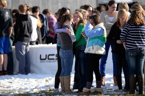 Students comfort each other as they stand on the football field after a gunman was spotted inside Arapahoe High School, Colorado on Dec. 13, 2013.