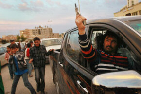 A Libyan man fires his pistol in the air during a celebratory rally, after the United Nations approved a no-fly zone over the country on March 18, 2011. See more gun pictures.