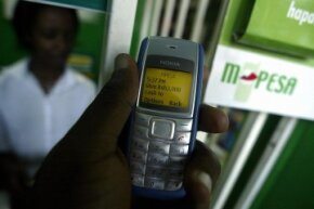 A man sends money through his phone using the M-PESA system.