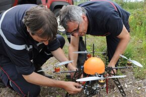 Two French firefighters prepare a drone during tests in the Landes forest region.