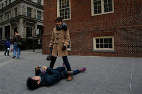 Hisashi Ueta, a Japanese student at Massachusetts General Hospital, lies down to get a better angle as he takes a picture of his wife. Foreign students like Ueta are exempt from certain taxes as they're considered nonresident aliens.