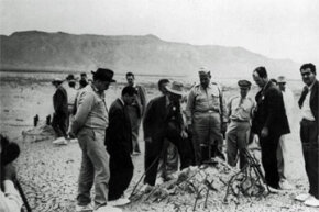 Officials from the Manhattan Project, the code name for the U.S. plan to develop atomic weapons, inspect the detonation site of the Trinity atomic bomb test. That's Dr. Robert J. Oppenheimer in the white hat.