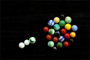 If you think of critical mass in terms of marbles, the tight formation of marbles represents critical mass and the three lone marbles stand in for neutrons.