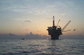 A spar production platform floats at sunset in the Gulf of Mexico. The structure's massive cylindrical hull extends down into the depths for hundreds of feet.