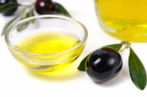 Olive oil, black olives, olive branches and a bottle of olive oil.