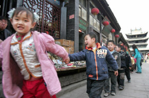 Children hold hands as they walk through the ancient city of Pingyao.