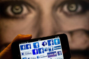 A man holds a smartphone displaying Facebook logo in front of a poster at the International Cyberbullying Congress in Berlin, Germany, in 2013.