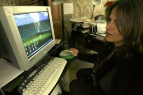 Khulud Dwaibess sits at her computer in her office in the West Bank city of Bethlehem. Several things happen when she boots up her computer, but eventually the operating system takes over.